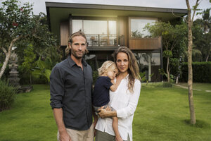 Portrait of smiling family standing in front of their design house surrounded by lush tropical garden - SBOF00803