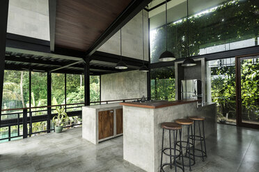 Modern minimalist kitchen in contemporary design house with glass facade surrounded by lush tropical garden - SBOF00806