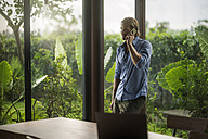 handsome man talking on smartphone in contemporary design house - SBOF00812