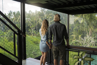 Couple looking at stunning view through glass facade in contemporary design house surrounded by lush tropical garden - SBOF00818