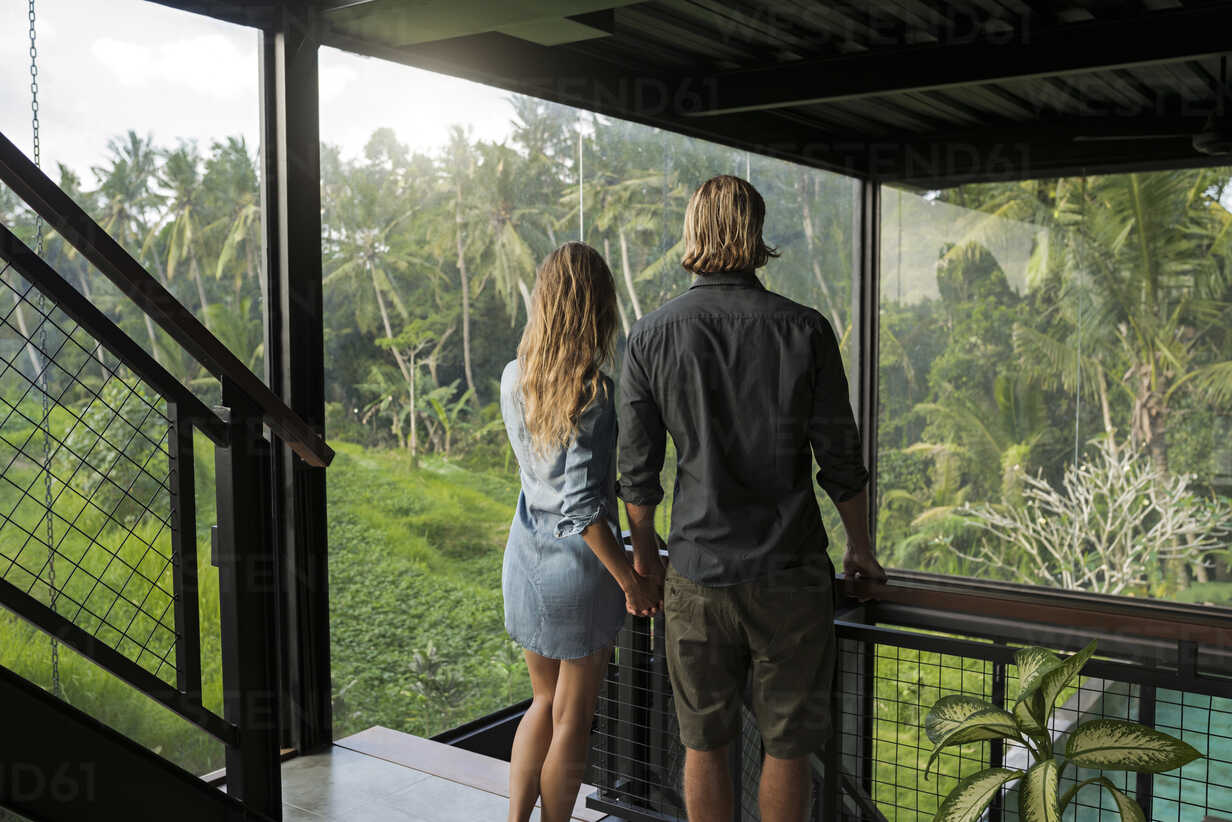 Couple looking at stunning view through glass facade in contemporary design house surrounded by lush tropical garden - SBOF00818 - Steve Brookland/Westend61