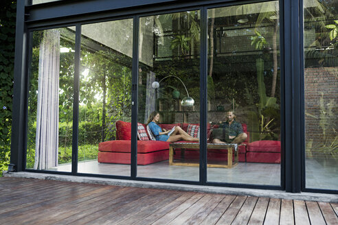 Garden view through glass facade of couple with laptop and book relaxing on red couch in modern design house - SBOF00821