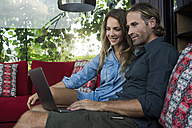 Smiling couple sitting on red couch looking at laptop in modern living room with glass facade in background - SBOF00824