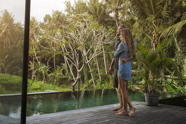 Hugging couple standing on wooden terrace in front of pool and enjoying stunning view in lush tropical garden - SBOF00827