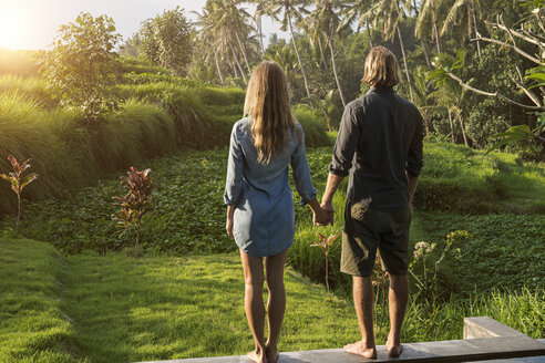 Couple holding hands while standing on the edge of a pool and enjoying stunning view of sunset in lush tropical garden - SBOF00830