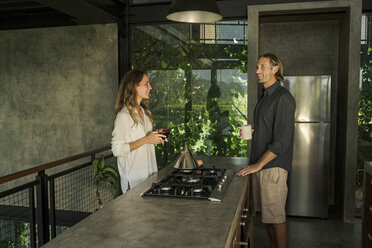 Couple having breakfast and smiling in modern design kitchen with glass facade surrounded by lush tropical garden - SBOF00833