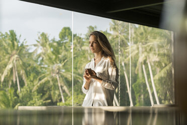Woman holding smartphone in design house in front of lush tropical garden - SBOF00836
