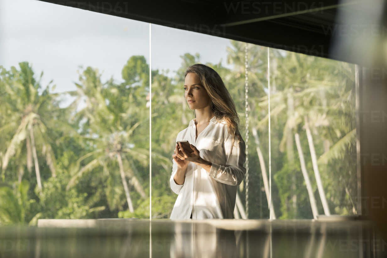 Woman holding smartphone in design house in front of lush tropical garden - SBOF00836 - Steve Brookland/Westend61