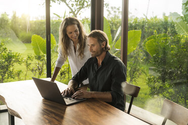 Woman smiling at husband working on laptop in design house surrounded by lush tropical garden - SBOF00839