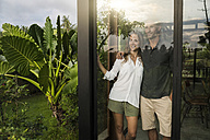 Successful couple looking outside of window of modern design house - SBOF00842