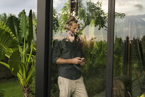 Handsome man standing behind glass facade of design house looking at smartphone surrounded by lush tropical garden - SBOF00845