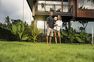 Portrait of smiling family standing in front of their design house surrounded by lush tropical garden - SBOF00848