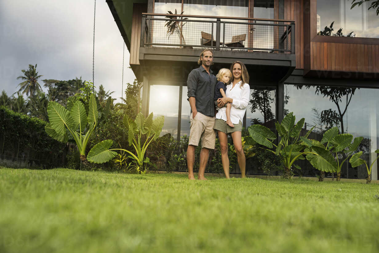Portrait of smiling family standing in front of their design house surrounded by lush tropical garden - SBOF00848 - Steve Brookland/Westend61