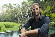 Portrait of handsome man in front of swimming pool and stunning tropical garden - SBOF00851