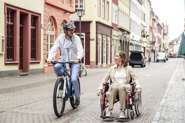 Germany, Heidelberg, woman in wheelchair and man on bicycle in the city - PNPF00004