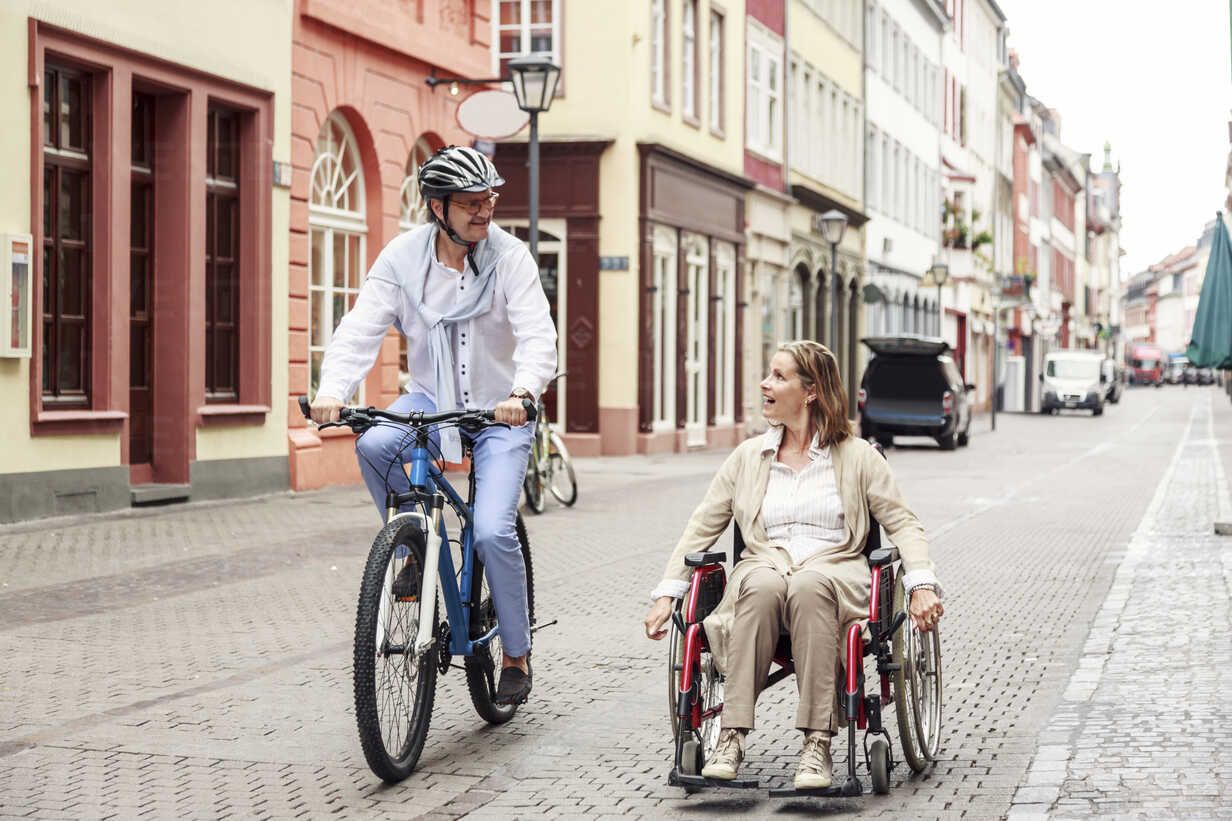 Germany, Heidelberg, woman in wheelchair and man on bicycle in the city - PNPF00004 - Nullplus/Westend61