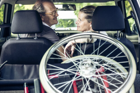 Smiling couple in car with wheelchair in boot - PNPF00013