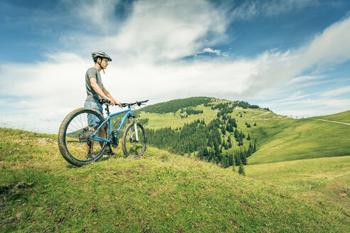 Germany, Bavaria, Pfronten, young man with mountain bike on alpine meadow near Aggenstein - PNPF00022