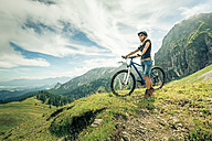 Germany, Bavaria, Pfronten, woman with mountain bike on alpine meadow near Aggenstein - PNPF00025