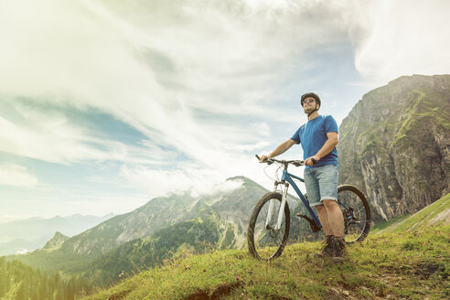 Germany, Bavaria, Pfronten, man with mountain bike on alpine meadow near Aggenstein - PNPF00028