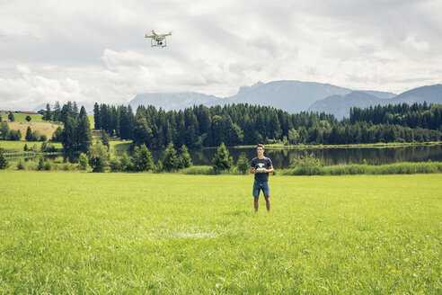 Germany, Bavaria, Pfronten, young man flying his drone at lakeside - PNPF00034