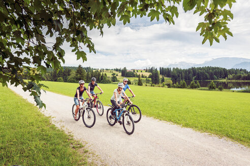 Germany, Bavaria, Pfronten, family riding mountain bikes at ladeside - PNPF00037