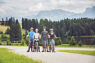 Germany, Bavaria, Pfronten, portrait of happy family with mountain bikes at ladeside - PNPF00040