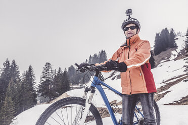 Austria, Damuels, woman with mountain bike and action cam in winter landscape - PNPF00043