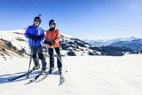 Austria, Damuels, couple with action cam skiing in winter landscape - PNPF00046