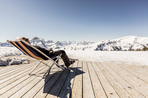 Austria, Damuels, senior man relaxing in deckchair on sun deck in winter landscape - PNPF00055