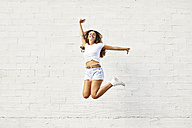 Happy young woman jumping mid-air in front of white wall - JRFF01447
