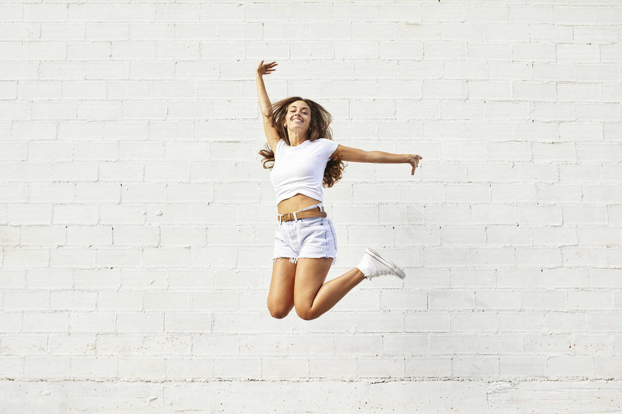 Happy young woman jumping mid-air in front of white wall - JRFF01447 - Josep Rovirosa/Westend61