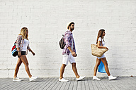 Three friends walking along white wall - JRFF01450