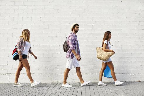 Three friends walking along white wall - JRFF01450