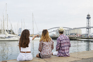 Spain, Barcelona, three tourists sitting on a pier in the city - JRFF01468