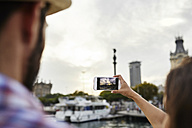 Spain, Barcelona, tourists taking a photo at the waterfront in the city - JRFF01471