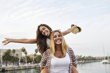 Spain, Barcelona, young woman giving her friend a piggyback ride - JRFF01474