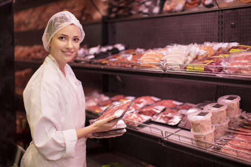 Portrait of smiling woman placing meat in display areas - ZEF14639
