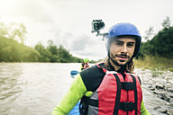 Germany, Bavaria, Allgaeu, portait of confident young man with action cam kayaking on river Iller - PNPF00061