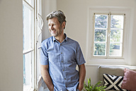 Mature man at home eaning at window - PDF01294