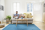Man sitting on couch at home, using smartphone - PDF01297