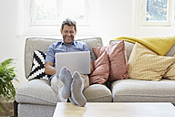 Man sitting on couch at home, using laptop - PDF01309