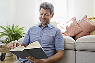 Mature man at home sitting in front of couch, reading book - PDF01312