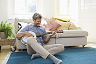 Man sitting on floor, playing the banjo - PDF01315