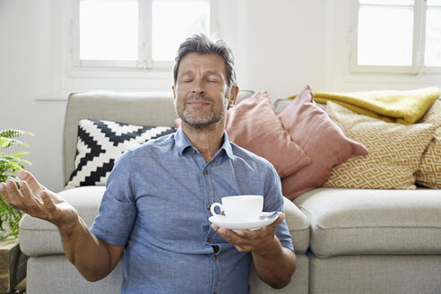 Mature man at home sitting in front of couch, drinking coffee - PDF01318