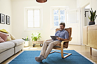 Man working at home using digital tablet - PDF01327