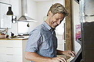 Mature man playing piano at home - PDF01339