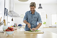Mature man in his kitchen chopping vegetables - PDF01342