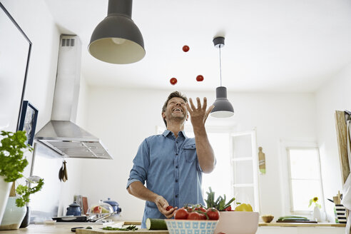 Mature man standing in kitchen, juggling with tomatoes - PDF01354
