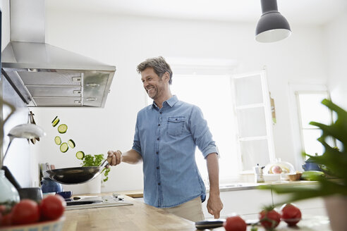 Mature man in his kitchen frying vegetables - PDF01357